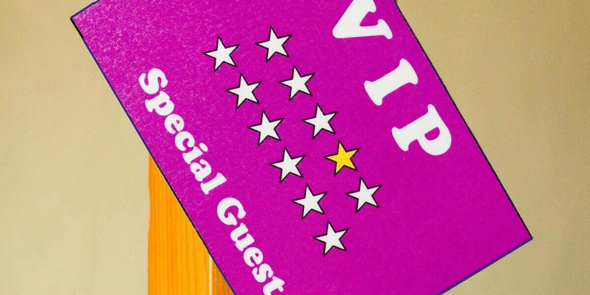 Rosa/lila VIP-kort med stjärnor och VIP samt special guest skrivet på det.