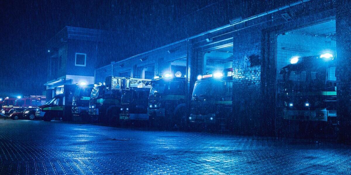 Utrycknigsfordon med blåljus på, parkerade med en regnig förgrund.